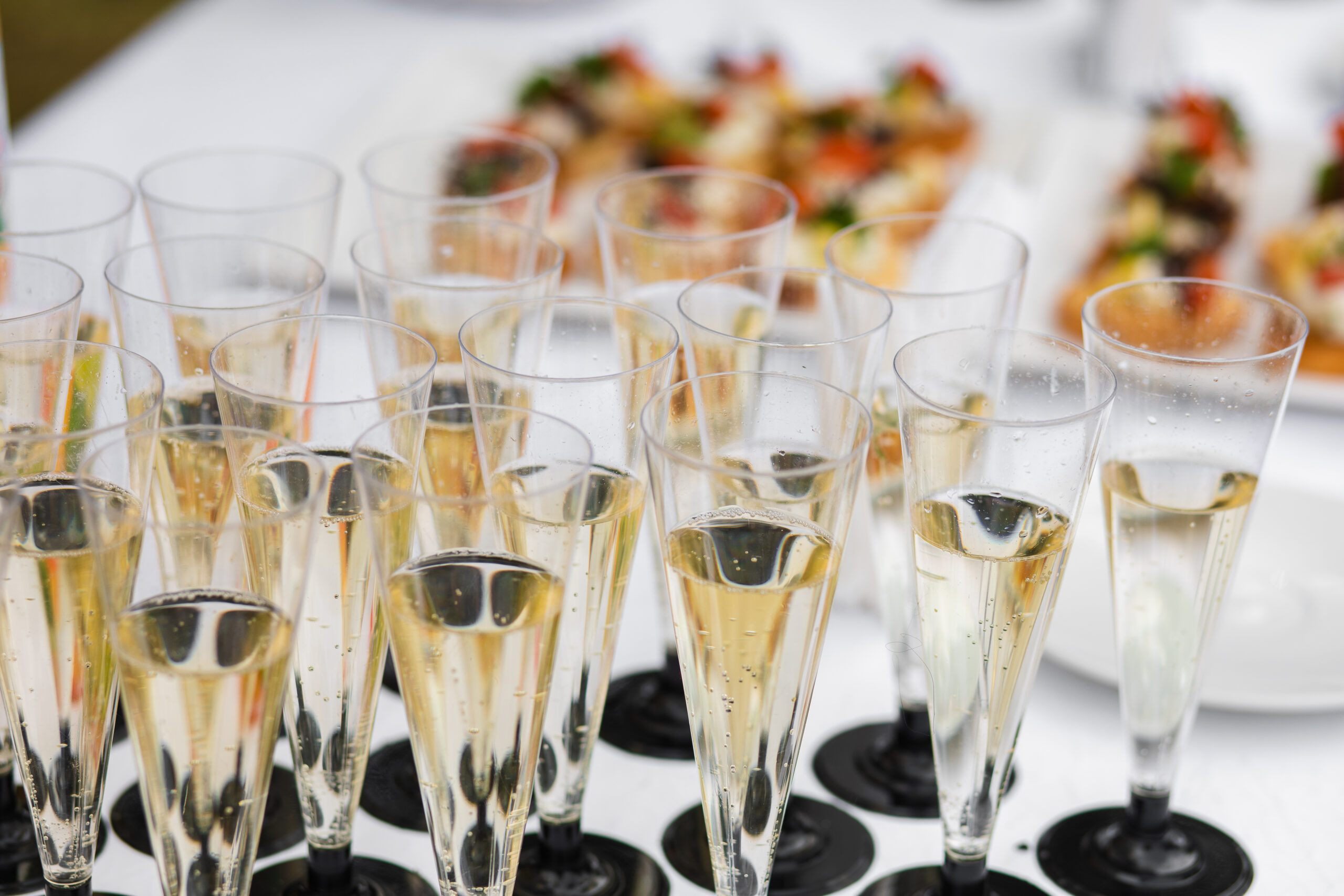 Glasses with champagne served on table near appetizers
